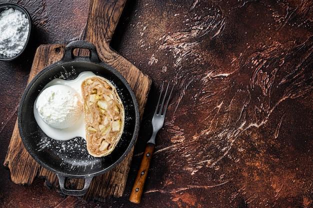 Apfelstrudelstrudel mit zimt, puderzucker und vanilleeis in einer pfanne