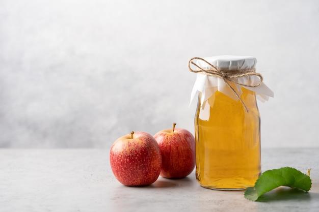 Apfelweinflasche und rote äpfel auf hellgrauem hintergrund
