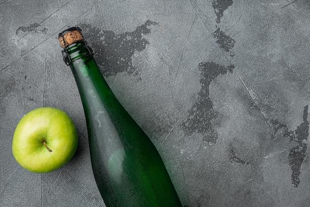 Apfelweinflaschenset, auf grauem steintischhintergrund, draufsicht flach, mit kopienraum für text