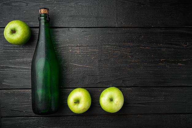 Apfelweinflaschenset, auf schwarzem holztischhintergrund, draufsicht flach, mit kopienraum für text