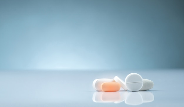 Apotheke drogerieprodukt. stapel der orange und weißen tablettenpille auf steigungshintergrund. tablettenpillen unterschiedlicher größe und form. pharmaindustrie. medizin im krankenhaus. retail-drogenmarkt.