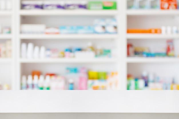 Apotheken-drogerie-thekentisch mit unscharfem abstraktem hintergrund mit arzneimitteln und gesundheitsprodukten in den regalen