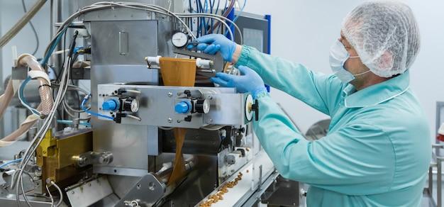 Apothekenindustrie-fabrikarbeiter in der schutzkleidung unter sterilen arbeitsbedingungen