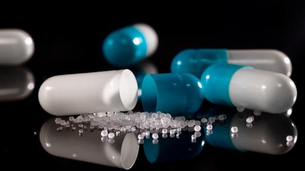 Apothekenoberfläche auf einem dunklen tisch. levitationspillen. tabletten auf einer dunklen oberfläche, die herunterfallen. tabletten. medizin und gesund. nahaufnahme von kapseln. pillen fallen auf schwarze oberfläche