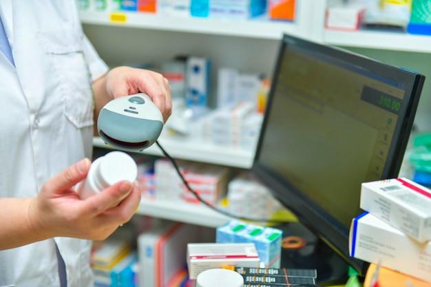 Apotheker, der barcode der medizindroge in einer apothekendrogerie scannt.