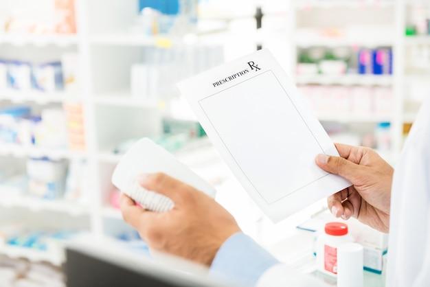 Apotheker, der die verordnung überprüft medizin in der apotheke hält