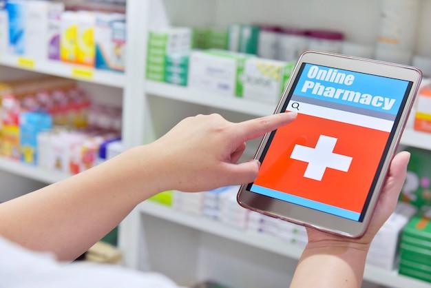 Apotheker, der ein touchpad für die suchleiste auf dem display im hintergrund der apothekenregale hält