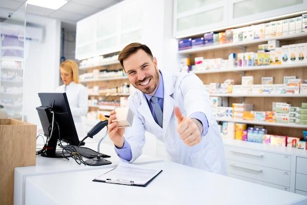 Apotheker, der medikamente in drogerie verkauft und daumen hoch hält.