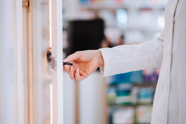 Apotheker, der medikation von einem regal, nahaufnahme nimmt.