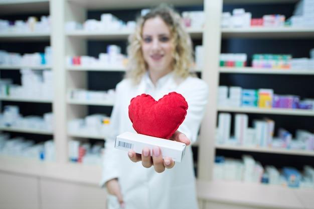 Apotheker in weißer uniform mit medikamenten gegen herz-kreislauf-erkrankungen