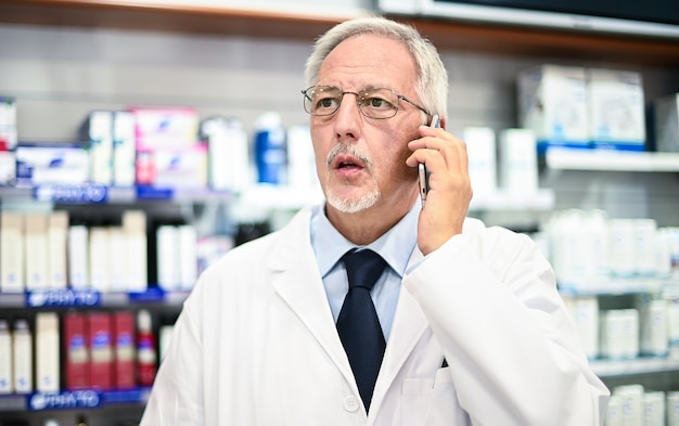 Apotheker telefoniert mit einem kunden in seinem laden