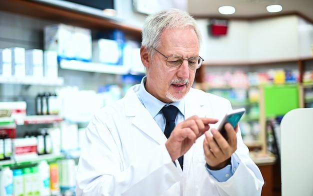 Apotheker überprüft sein smartphone, während er in seinem geschäft arbeitet
