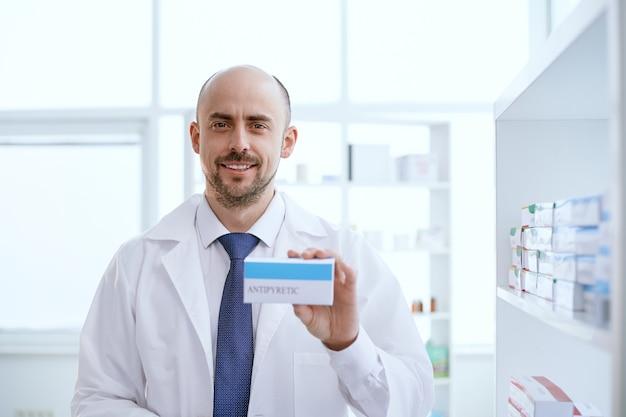Apotheker zeigt eine schachtel mit einem neuen medikament