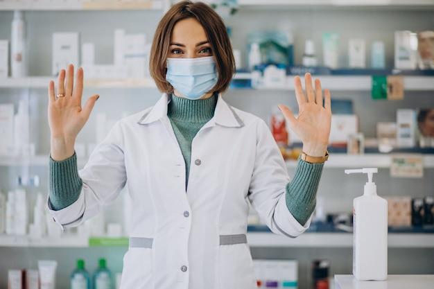 Apothekerin der jungen frau desinfiziert hände mit sanitazer