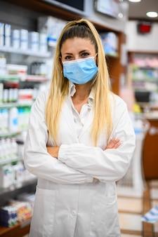 Apothekerin mit schutzmaske im gesicht, die in der apotheke arbeitet. medizinisches gesundheitskonzept.