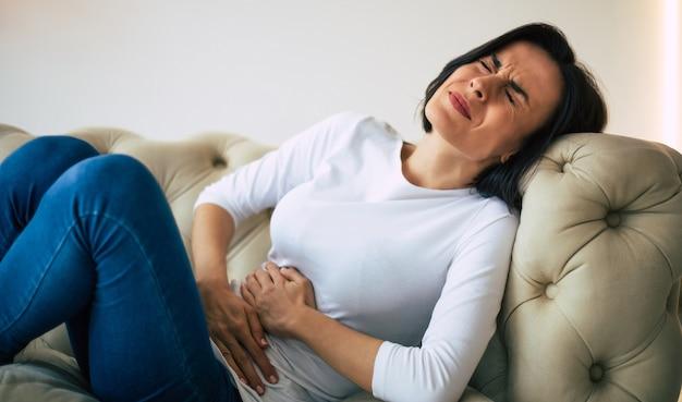 Appendizitis. erwachsene junge frau liegt auf einem sofa und hält sich den bauch, während sie unter unerträglichen schmerzen leidet.