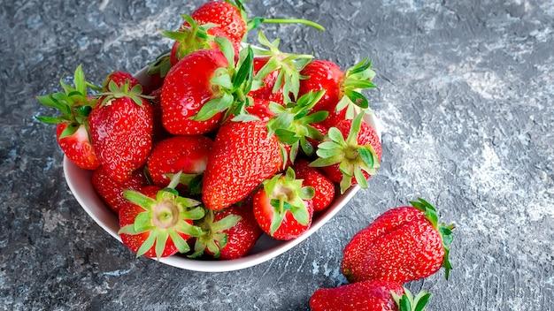 Appetitanregende erdbeere in der schüssel auf einem grauen hintergrund.