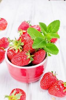 Appetitanregende erdbeere in der schüssel auf einer weißen tabelle