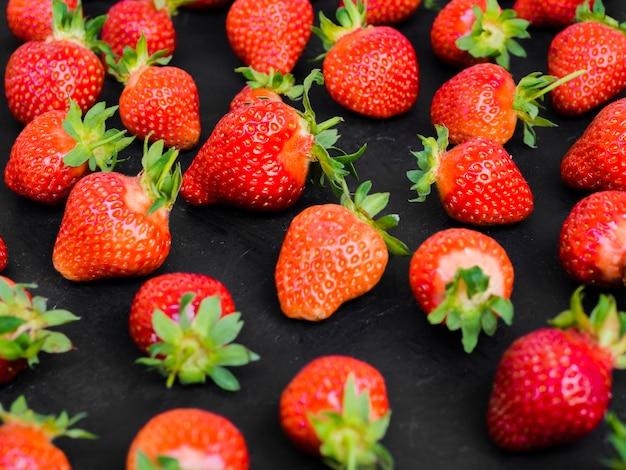 Appetitanregende erdbeeren auf dunkler tabelle