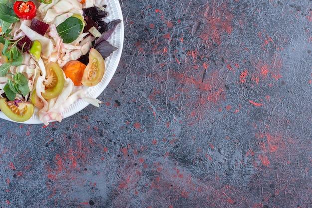 Appetitanregende essiggurkenplatte angezeigt auf dunklem farbigem hintergrund. foto in hoher qualität