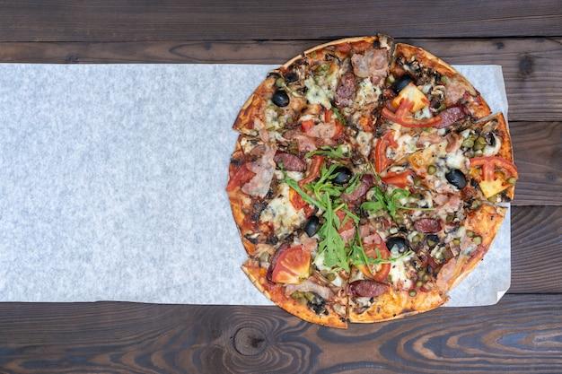 Appetitanregende pizza mit pappschachteln des geräucherten wurstspeckfleisch-tomatenkäse-rucola für lieferung auf schwarzer dunkelheit. mit copyspace