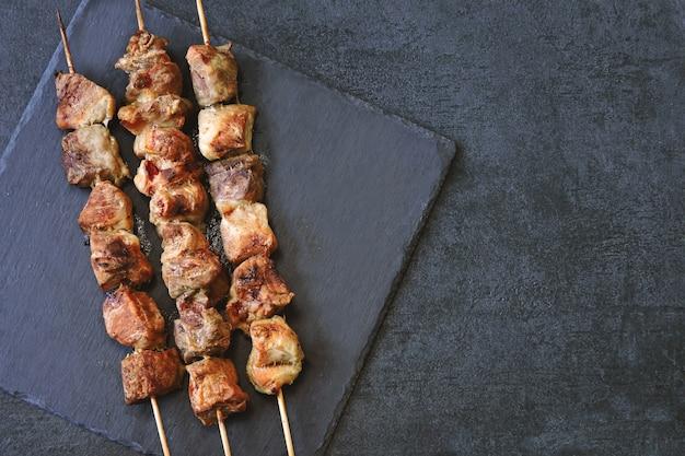 Appetitanregende rötliche kebabs auf einer dunklen steinoberfläche. ansicht von oben.