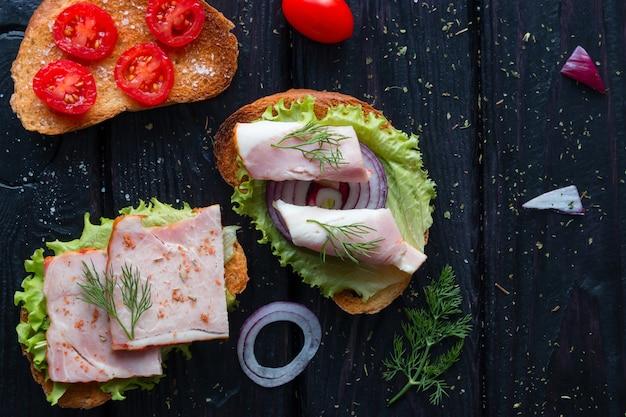 Appetitanregende sandwiche mit fleisch- und gemüsegewürzen auf schwarzer tabelle
