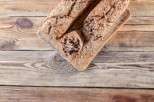 Appetitanregende stangenbrote mit samen und nüssen des indischen sesams auf einem schneidebrett auf einem hölzernen hintergrund.