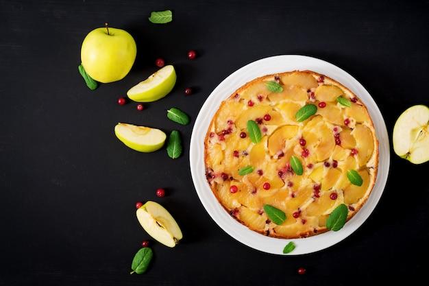 Appetitanregende torte mit äpfeln und preiselbeeren auf einem schwarzen tisch. draufsicht. flach liegen