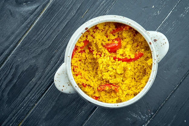 Appetitanregende und diätetische orientalische beilage - couscous-brei mit gemüse, serviert in einem weißen topf auf schwarzem holzhintergrund