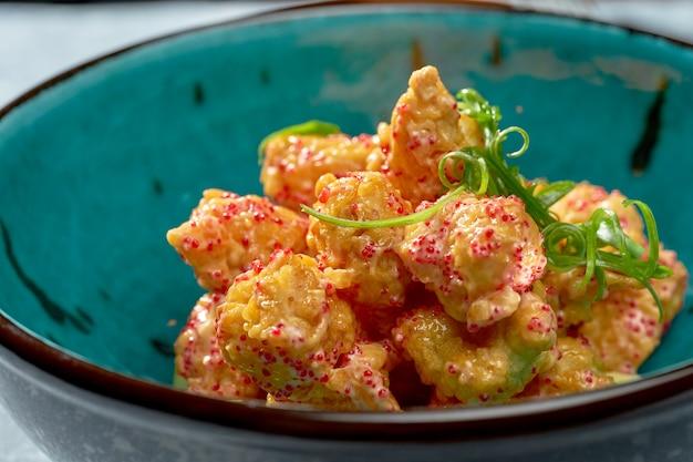 Appetitanregende vorspeise - frittiertes garnelen-popcorn mit sauce, tobiko-kaviar und avocado in einer blauen schüssel auf grauem hintergrund. nahaufnahme, selektiver fokus