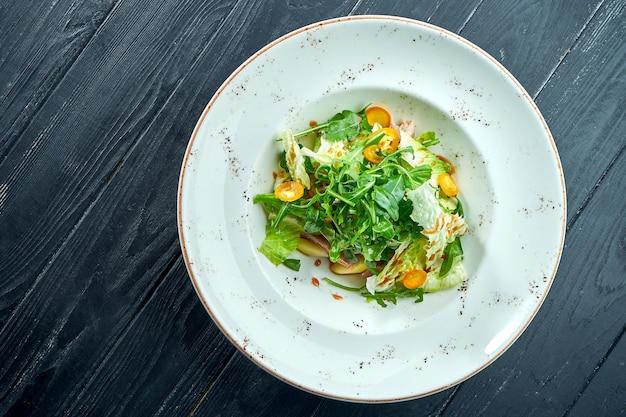 Appetitanregender, diätetischer salat mit rucola, sauce, salat und warmem rindfleisch in einem weißen teller auf dunkler holzoberfläche. gesundes essen