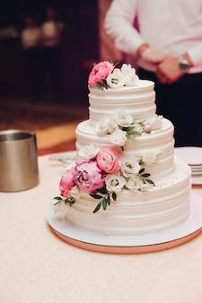 Appetitanregender frischer gebäckkuchen bedeckt durch weiße sahneglasur und verzieren die süße blumenumhüllung auf tabelle Premium Fotos