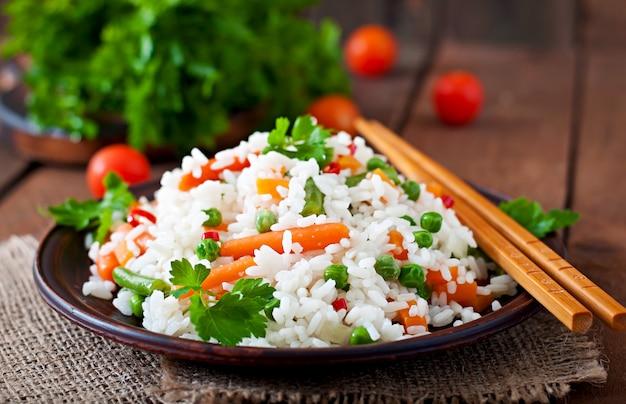 Appetitanregender gesunder reis mit gemüse im weißen teller auf einem holztisch.