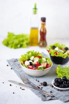 Appetitanregender griechischer salat in einer platte auf einer gedienten tabelle