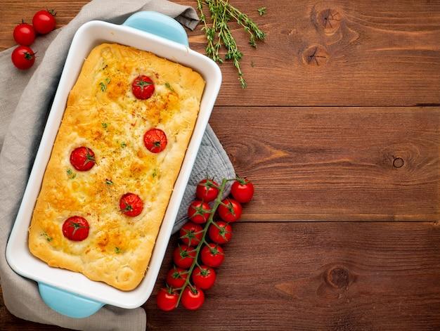 Appetitanregendes goldenes focaccia mit tomaten und gewürzen, auf dunkler hölzerner rustikaler tabelle