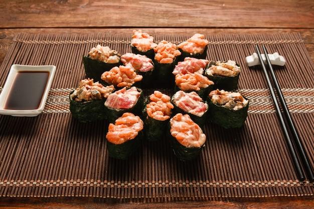 Appetitanregendes japanisches sushi. satz leckere brötchen, serviert auf brauner strohmatte, nahaufnahme. restaurantmenüfoto, traditionelle gesunde meeresfrüchte, lebensmittelkunst.