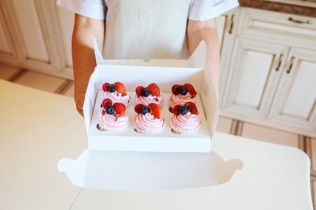 Appetitlich cremige cupcakes mit frischen beeren in der schachtel in den frauenhänden, dessert-lieferkonzept.