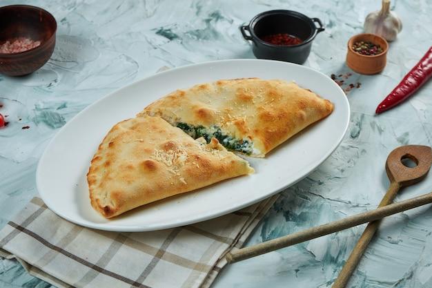 Appetitlich frisch gebackene calzone-pizza mit knusper in einem weißen teller auf einem grauen tisch. restaurant servieren.