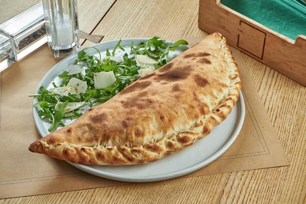 Appetitlich frisch gebackene calzone-pizza mit knusper in einem weißen teller auf einem holztisch. restaurant servieren.