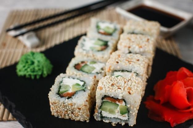 Appetitlich frische kalifornische sushi-rolle mit lachs in sesam serviert auf schwarzem schiefer mit ingwer und wasabi, nahaufnahme. japanische gesunde meeresfrüchte.