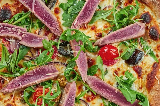 Appetitlich gebackene pizza mit thunfisch, rucola, kirschtomaten und parmesan mit knusper auf einem holztisch. restaurant servieren. pizza mit meeresfrüchten. draufsicht, nahaufnahme auf textur