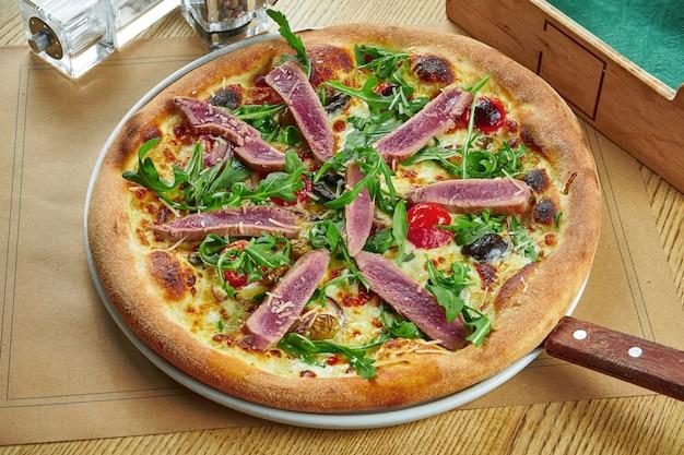 Appetitlich gebackene pizza mit thunfisch, rucola, kirschtomaten und parmesan mit knusper auf einem holztisch. restaurant servieren. pizza mit meeresfrüchten