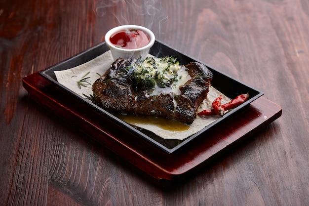 Appetitlich gegrillte fleischgerichte mit sauce auf einem dunklen holztisch.