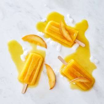 Appetitlich schmelzendes eis auf einem stock mit einem muster von spritzer von eiswürfeln und pfirsichstücken auf einem grauen marmorhintergrund kopieren raum. flach liegen