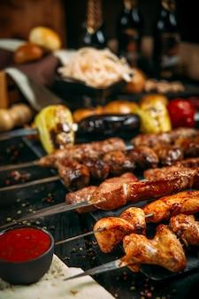 Appetitliche auswahl an kebab-spießen mit roter sauce und eingelegten zwiebeln auf einem schwarzen brett