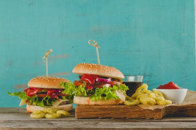 Appetitliche burger mit zwiebelringen und trinken