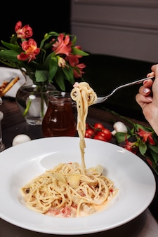 Appetitliche carbonara-paste mit hühnchen, das nicht richtig auf die gabel gewickelt ist. spaghetti hängen ungenau und fallen von der gabel. nahansicht.
