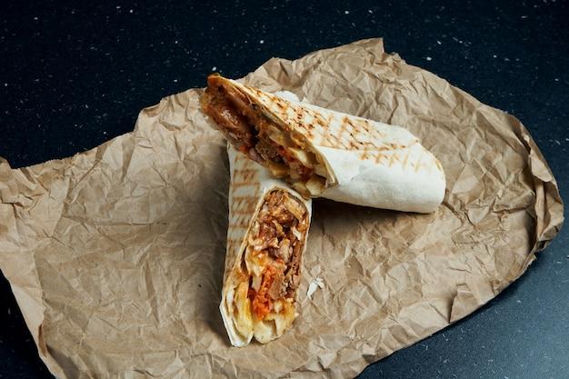 Appetitliche dönerrolle mit fleisch, salat und hausgemachter sauce in dünnem fladenbrot auf bastelpapier auf einem schwarzen tisch. östliche küche. geschnittener kebab mit gegrilltem fleisch.