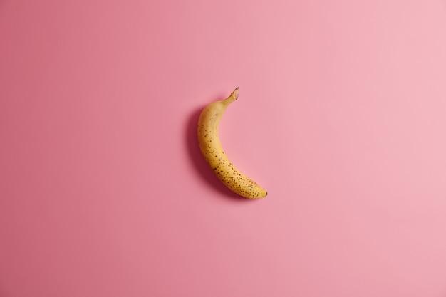 Appetitliche frische ganze gelbe banane lokalisiert auf rosa hintergrund. leckeres ungeschältes obst zum frühstück. horizontale aufnahme. reife früchte mit viel kalorien und vitaminen. sauberes esskonzept.